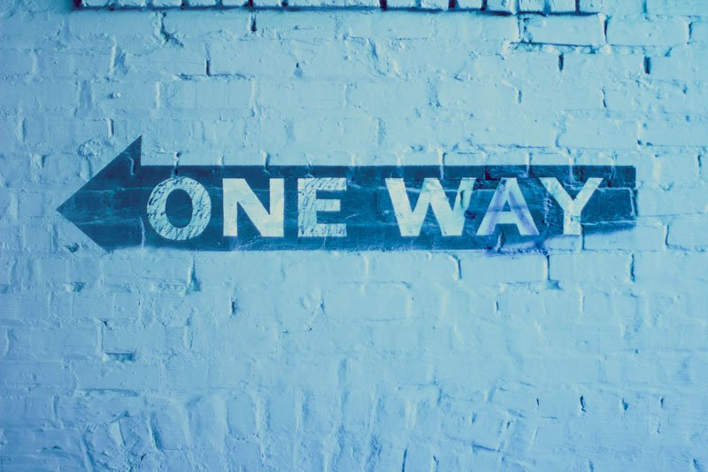Image of One Way sign painted on brick wall