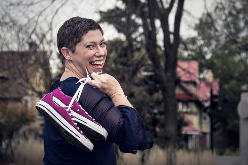 Tricia looking over her shoulder with the shoelaces of raspberry colored sneakers looped over her finger